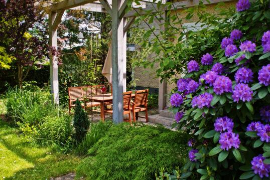 Idee für eine kleine Außenterrassse mit Sitzgruppe aus Holz – Blühender Rhodo...