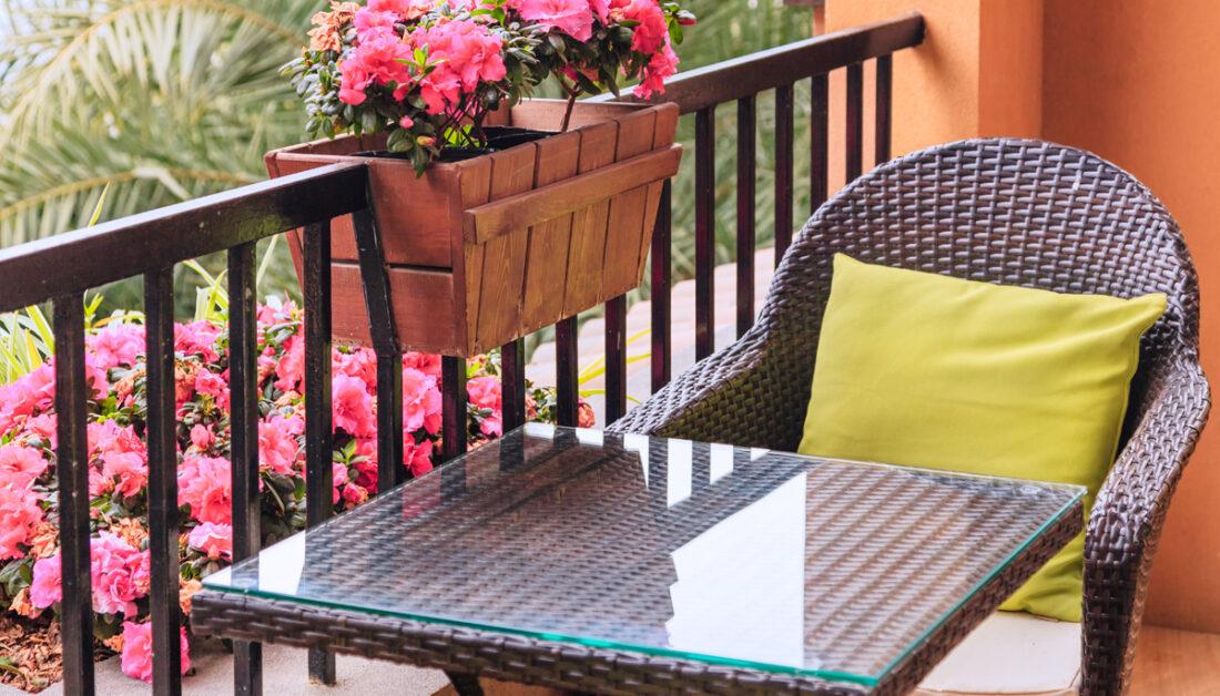 Balkon Idee - Kleiner gemütlicher Balkon mit pinken Rhododendren im Blumenkasten aus Holz - Sitzgruppe mit Rattanstuhl & Rattantisch - Kissen & Polsterung auf dem Stuhl