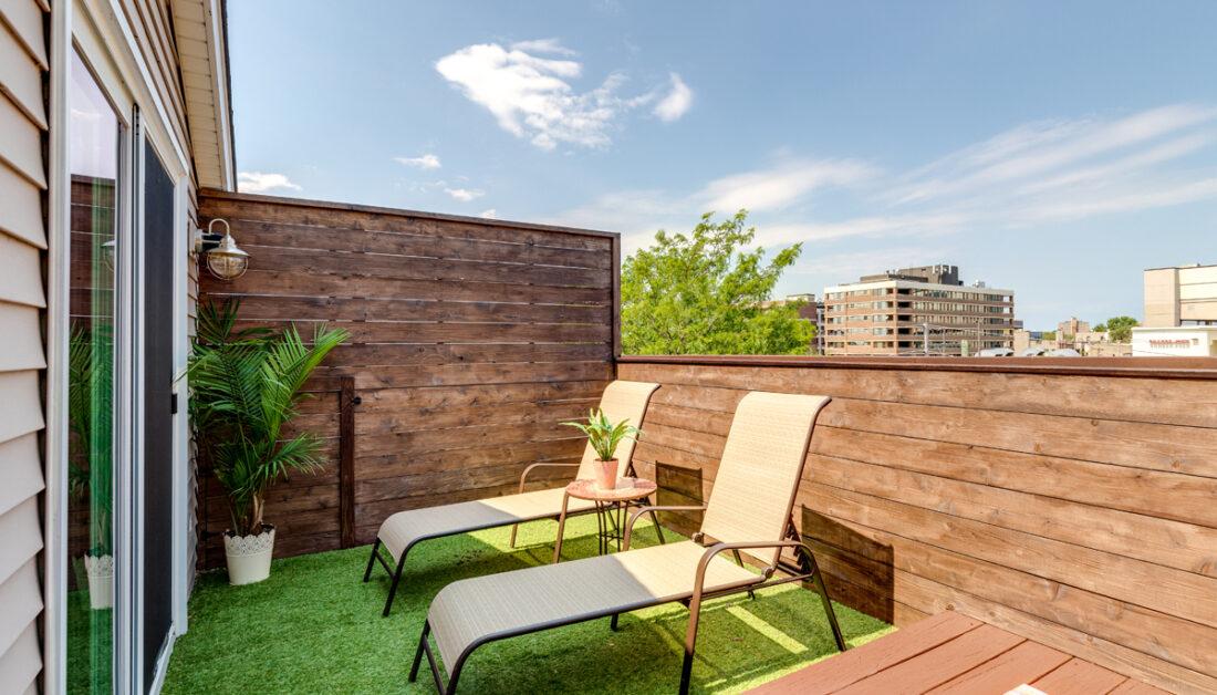 Balkon Idee mit Sichtschutz aus Holz & zwei Sonnenliegen - Metallbeistelltisch mit Pflanze - Außenwandleuchte - Balkonboden mit Kunstrasen