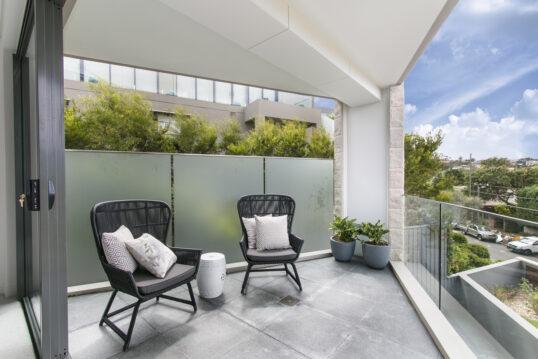 Moderne Balkon Idee mit Sichtschutzwand aus Glas & gemütlichen Stühlen –...