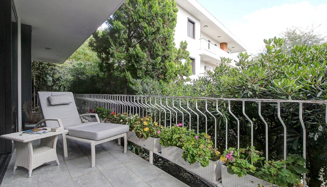 Moderne Idee für einen großen Balkon am Haus - Beispiel mit Rattansonnenliege & Rattantisch - Gemütliche Outdoor Polsterauflage - Bepflanzte Blumenkästen am Balkongeländer