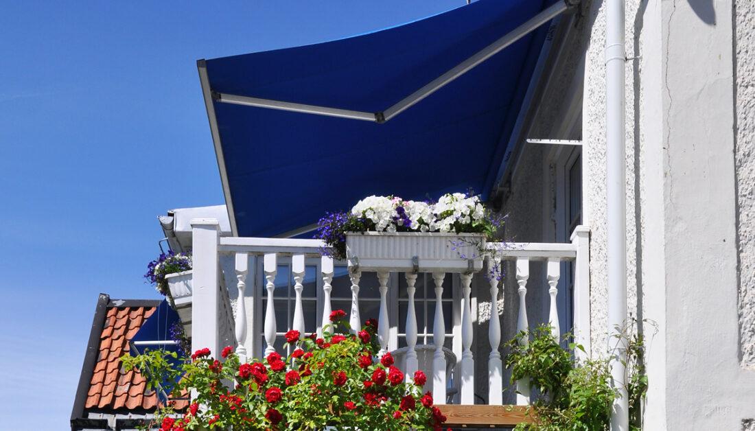 Beispiel für die Balkongestaltung - Idee mit blauer Markise als Balkon Sonnenschutz - Blumenkästen am weißen Balkongeländer