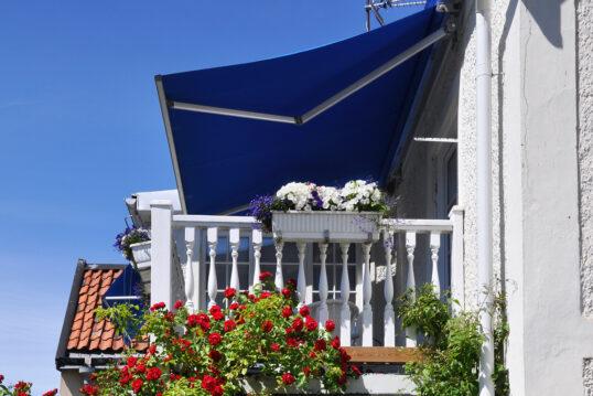 Beispiel für die Balkongestaltung – Idee mit blauer Markise als Balkon Sonnen...