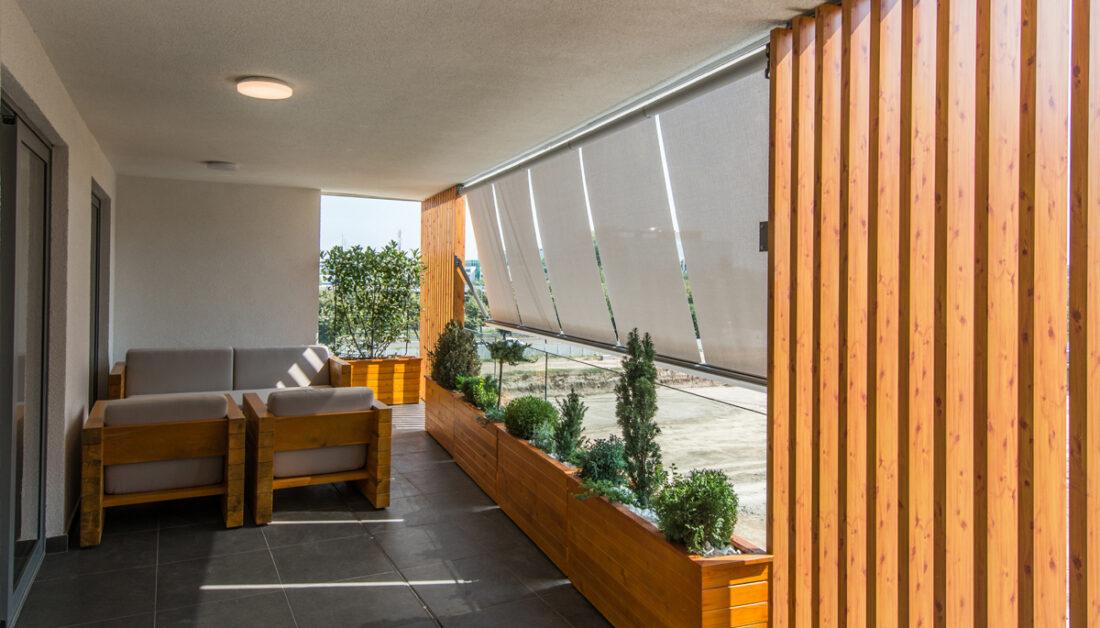 Idee für die Balkongestaltung - Moderner Balkon mit Markisen als Sonnenschutz & Sichtschutzwand aus Holz - Sitzgruppe mit Retrosesseln - Außenbeleuchtung an der Überdachung