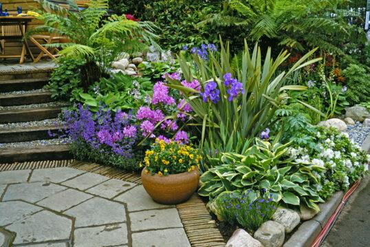 Gartenidee – Gartenaufgang zur Terrasse mit bepflanzten Beet neben der Treppe...