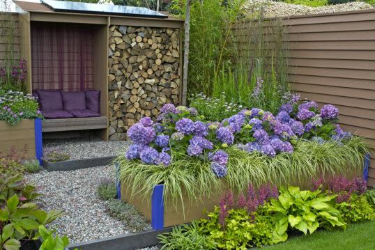 Gestaltungsbeispiel für den Garten – Idee mit Blumen Hochbeet bepflanzt mit l...