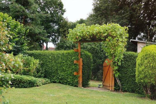Beispiel für den Garteneingang mit Gartentor & bepflanzten Torbogen am Hang &#...