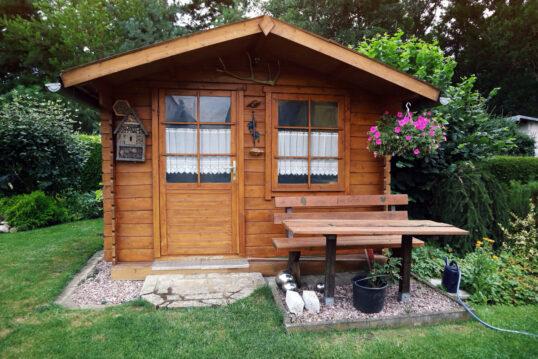 Idee für den Garten im Landhausstil mit Gartenhaus aus Holz & Sitzbereich R...