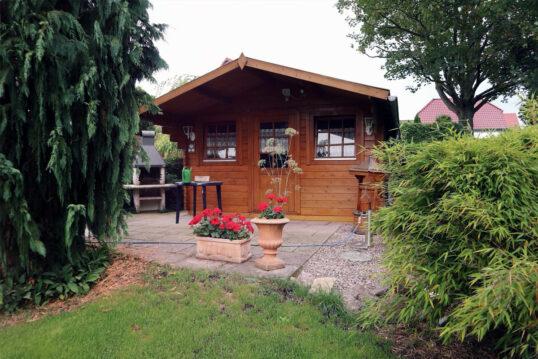 Gartenidee mit Gartenhaus aus Holz & gepflasterter Terrasse – Beispiel m...