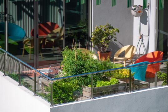 Gestaltungsidee für einen großen Balkon – Beispiel mit Hochbeeten  farbige Po...