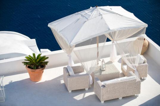 Idee für einen großen Balkon mit weißer Rattansitzgruppe  Laterne & Sonnenschi...