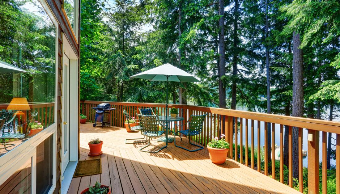 Großer Balkon oder Terrasse um das Haus - Gestaltungsidee mit Sitzgruppe & Sonnenschirm - Pflanzgefäße & Gartengrill - Fußmatte vor der Haustür