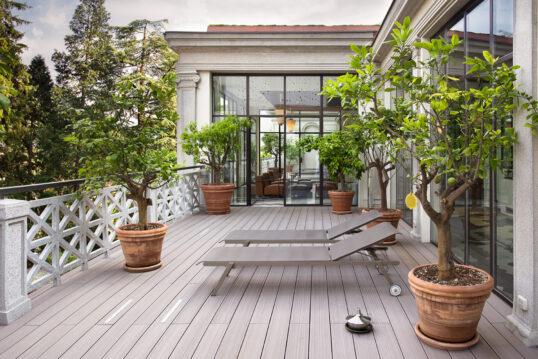 Balkon Idee - Beispiel für einen großen luxuriösen Balkon mit Rollliegen - Pflanzgefäße mit Zitrusbäumen - Balkonboden aus Holz
