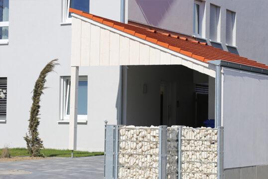 Haus Idee mit einem nachträglich hinzugefügten Vordach – Gabionenzaun als Sic...
