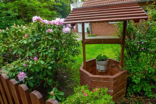 Idee für die Gartendekoration – Kleiner Holzbrunnen als Deko im Garten neben ...