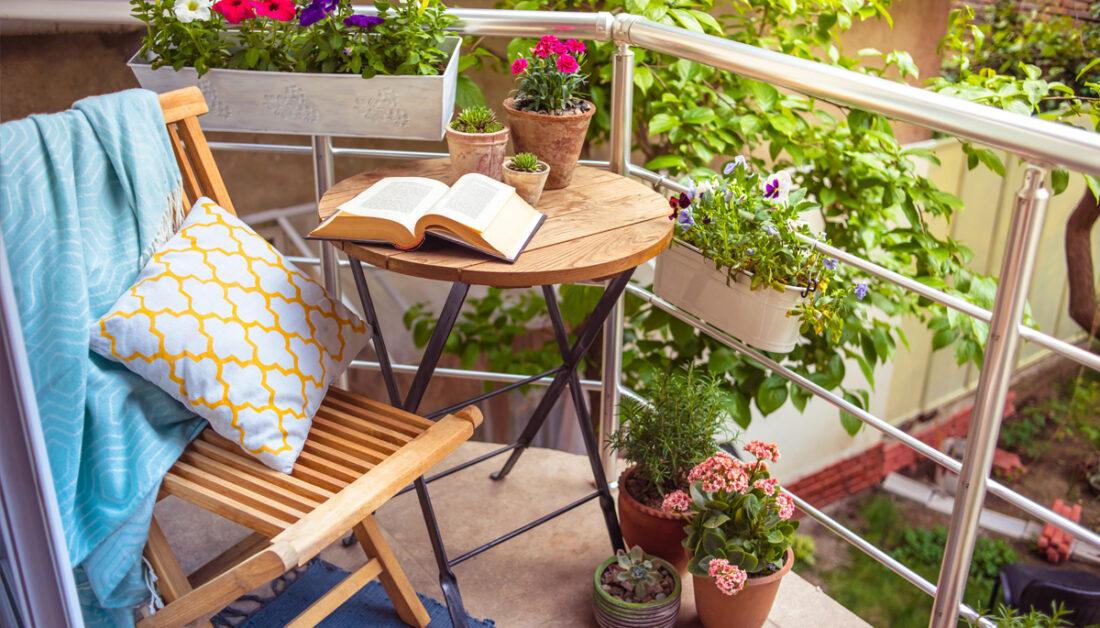 Idee für einen kleinen Balkon - Beispiel mit Klapptisch & Klappstuhl mit Kissen & Decke - viele kleine Pflanzgefäße mit Blumen - Blumenkasten am Balkongeländer