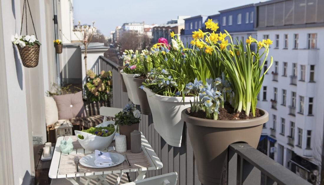 Romantisches Beispiel für einen kleinen schmalen Balkon mit Sitzgruppe - Idee mit weißen Tisch mit Stühlen  Blumentöpfe & Blumenkästen am Balkongeländer - Blumenampeln an der Hauswand
