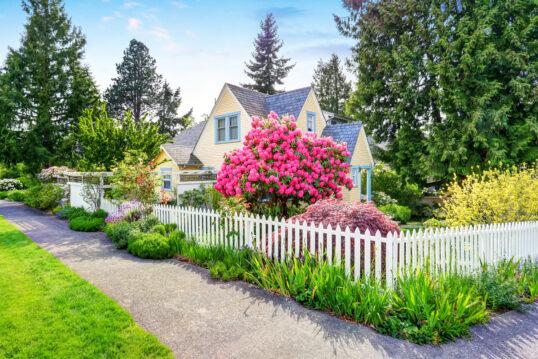 Garten Gestaltungsidee – Kleines gelbes Haus mit weißem Zaun & blühenden...