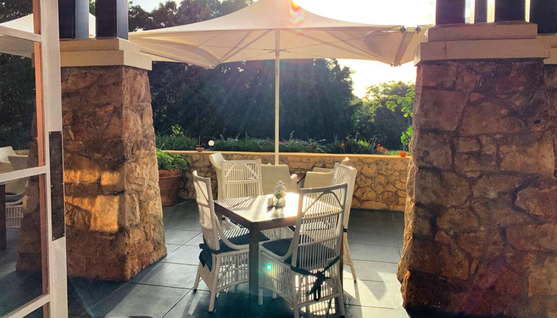 Landhaus Balkon Idee mit Korbstühlen & Holztisch - Balkon Sonnenschutz mit Sonnenschirm - kleine Laterne als Tischdekoration & Polsterauflagen