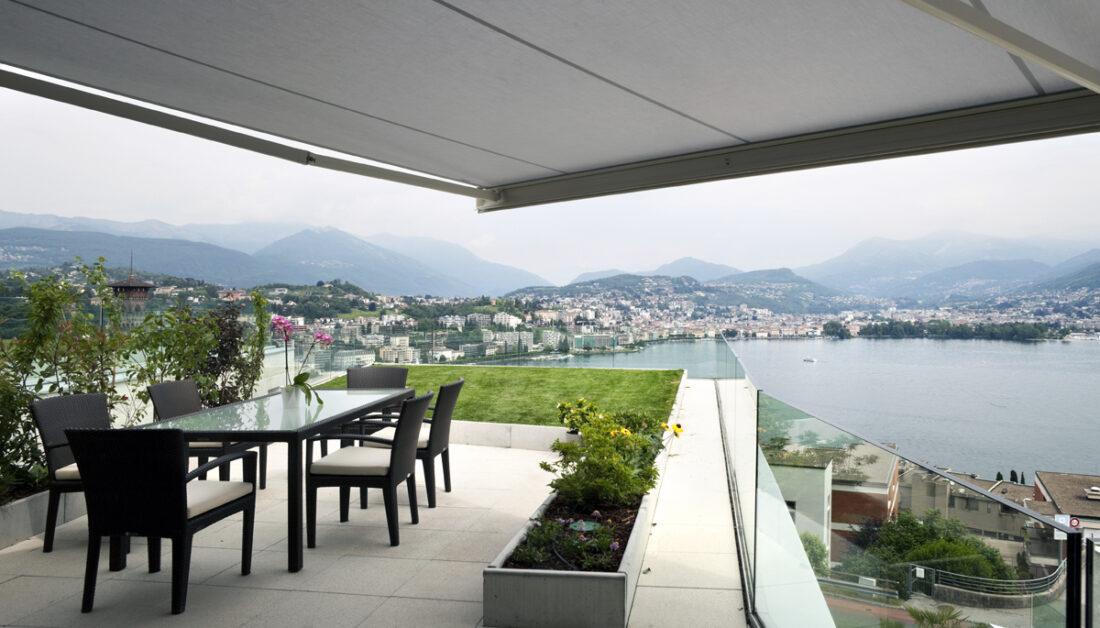 Balkon Idee - Großer Luxus Balkon mit schwarzer Sitzgruppe aus Polyrattan & Balkonmarkise als Sonnenschutz & Überdachung - Pflanzen & Rasenfläche