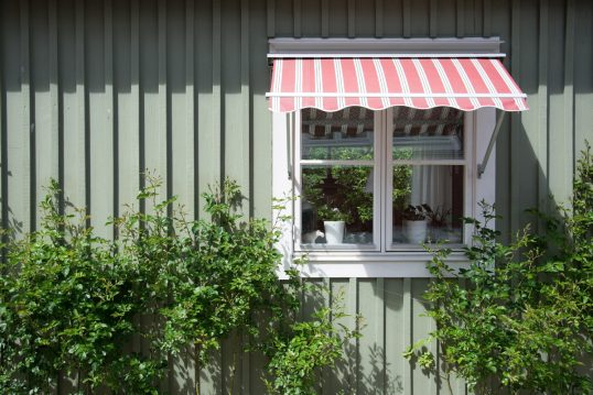 Hauswand Idee im Landhausstil – Rot gestreifte Gelenkarm-Markise außen am Fen...