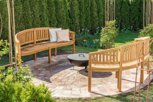 Terrassen Idee - Runde Terrasse mit Holzbänken um die Feuerschale aus Metall - Beispiel mit bepflanzten Beeten mit Blumen & Sträuchern