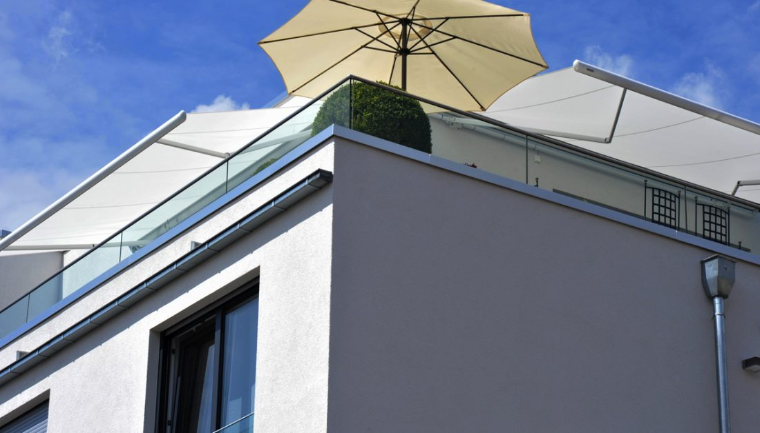 Sonnenschutz Idee für den Balkon oder die Dachterrasse - Beiger Sonnenschirm & weiße Sonnenschutzmarkisen an der Hauswand - Großer Buchsbaum als Balkon Dekoration