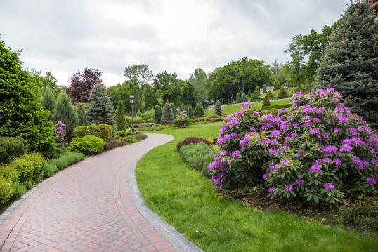 Gestaltungsidee für einen Park – Beispiel mit gepflasterten Parkweg entlang v...