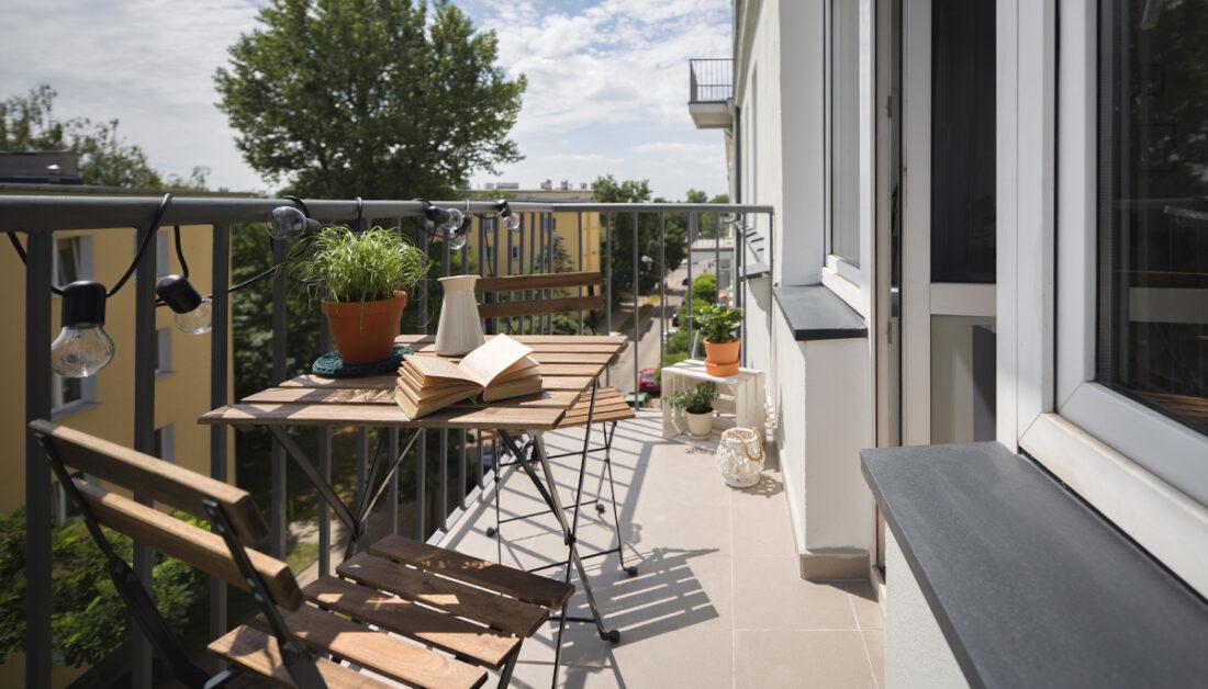 Gestaltungsidee für einen schmalen Balkon mit Sitzgruppe aus Holz - Blumentöpfe & Pflanzgefäße mit Balkonpflanzen - Dekoration mit Vase  Laterne und Lichterkette