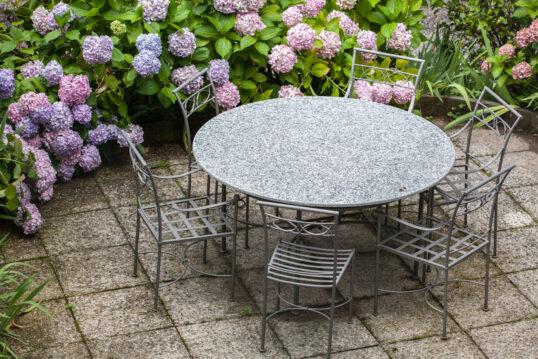Gartenidee – Sitzgruppe aus Metall auf der Terrasse umgeben von lila & r...