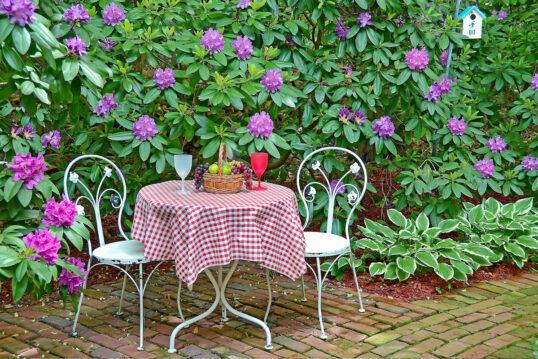Garten Gestaltungsidee – Sitzgruppe aus Metall vor lila Rhododendron – ...