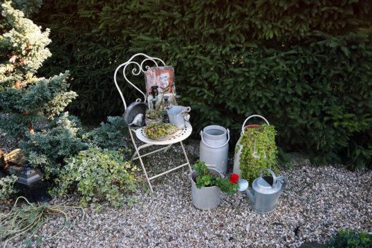 Gestaltungsidee für einen kleinen Steingarten an der Hecke  dekoriert mit Stuhl  Pf...