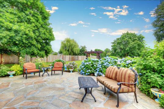 Terrassen Idee – Große runde Terrasse mit Bank  Sesseln & Tischen aus Me...