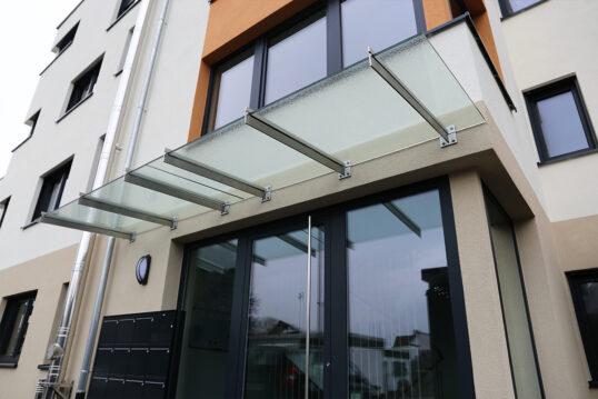 Idee für die Vordachgestaltung am Mehrfamilienhaus – Beispiel mit Glasvordach...