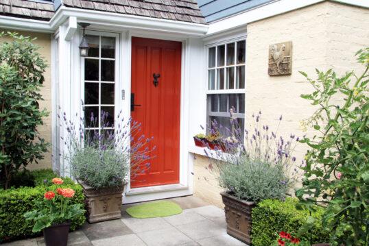 Charmanter Hauseingang mit roter Haustür – Idee mit Lavendel in Pflanzkübeln  gepflegte Buchsb...