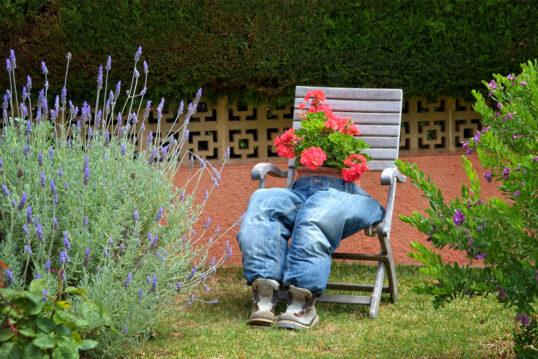 Deko Idee für den Garten – Klappstuhl mit lustiger Gartendekoration & roten Rhododendren – Gr...