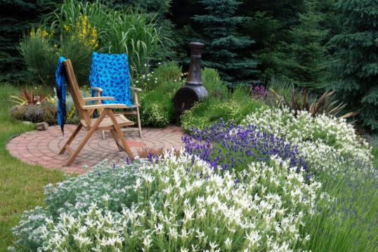 Landhaus Gartenidee – Kleiner Sitzbereich im Garten mit zwei Klappstühlen & Gartenofen umgeben von ...