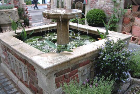 Idee für die Gartengestaltung – Beispiel mit großen Steinbrunnen in der Mitte...