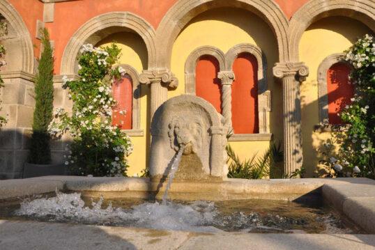 Beispiel für die Gartengestaltung – Großer Steinbrunnen mit Wasserspeier Löwe...