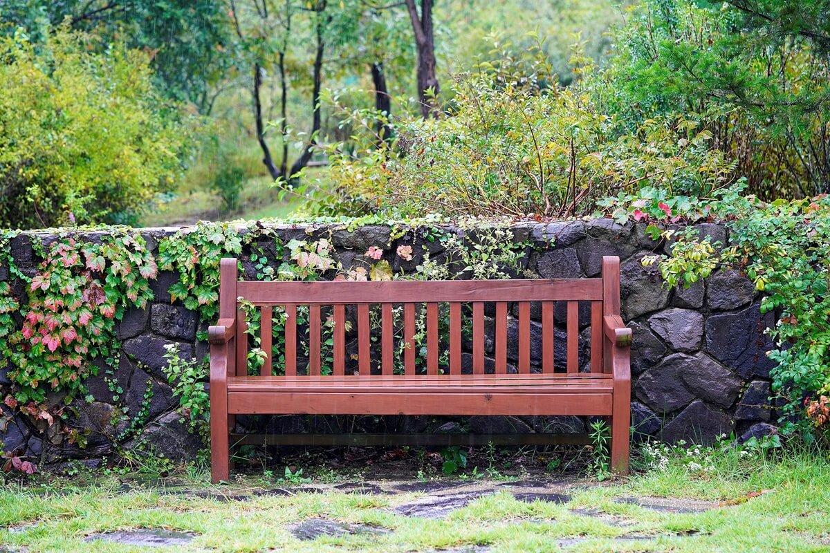 Gestalte deinen Gartenrand mit einer schönen Steinmauer oder Hecke, die zugleich vor ungewollten Blicken schützt.
