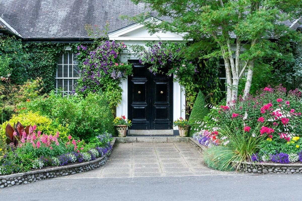 Gestalte deinen Vorgarten mit schönen Dekorationen und zierenden Gewächsen, die zum Verweilen einladen.