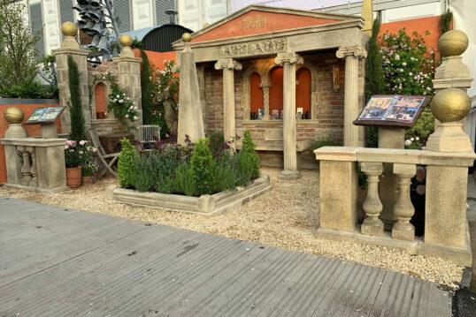 Gestaltungsbeispiel mit Gartenruine - Dreiseitige Gartenruine mit Steinmauern & angedeutetes Gebäude - Beet mit Pflanzen & Sitzplatz