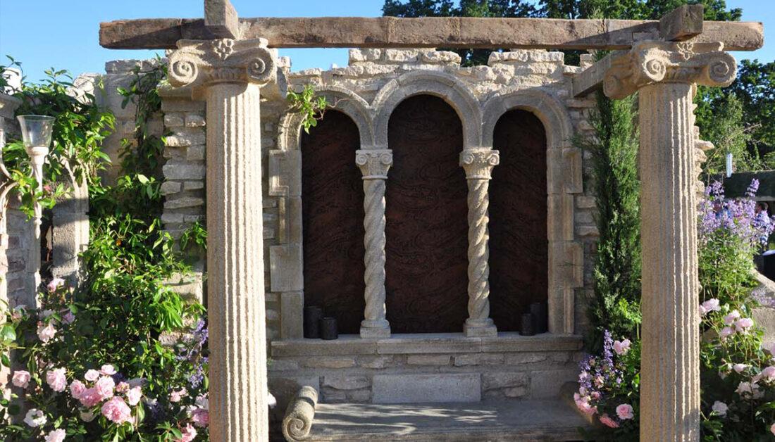 Gartendeko Idee - Element einer Gartenruine im gotischen Stil mit Säulen & Steinbank - Rosen links & rechts von der Ruine