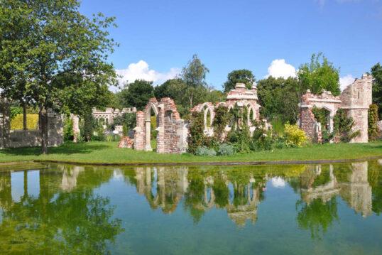 Beispiel für die Gestaltung eines großen Gartens - Gotische Gartenruinen-Elemente als Gartendekoration auf der Wiese neben dem Schwimmteich