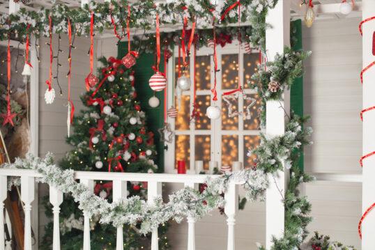 Idee für die Vordach-Gestaltung mit Weihnachtsdeko - Beispiel mit Weihnachtskugeln & Weihnachtsgirlanden - Weihnachtsbaum neben dem Fenster