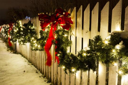 Gartenidee mit Weihnachtsdeko – Beispiel mit weihnachtlicher Dekoration am weißen Gartenzaun – Große rote Schleifen an der Weihnachtsgirlande & Lichterketten