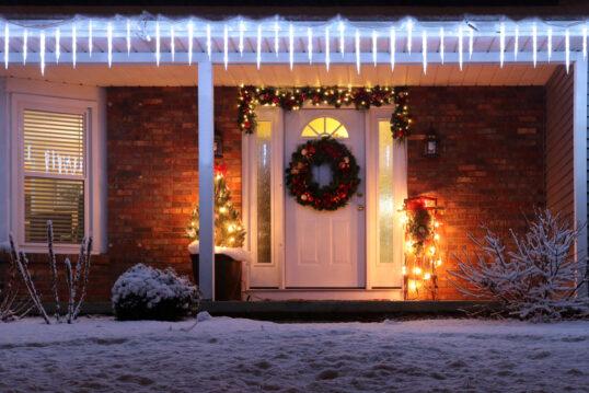 Idee für ein Wohnhaus mit Weihnachtsdeko außen - Beispiel mit Weihnachtskranz & Weihnachtsgirlande an der Haustür - Geschmückter Weihnachtsbaum im Pflanzgefäß