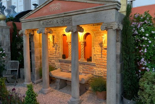 Idee für den Garten - Beleuchtete Gartenruine mit Säulen & rustikaler Steinbank - Bepflanzte Pflanzgefäße neben der Bank - Kiesboden