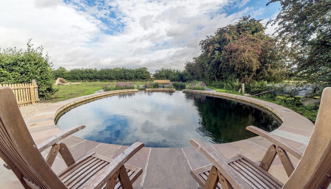 Moderner Schwimmteich mit angrenzender Terrasse - Beispiel mit Klappstühlen zum Entspannen nach dem Schwimmen