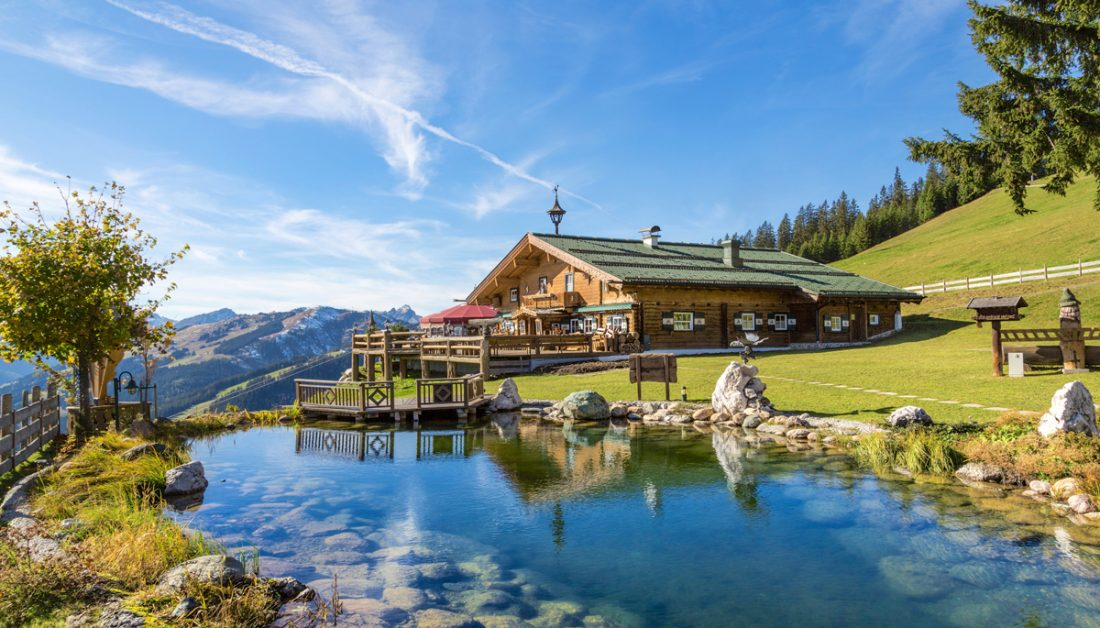 Garten Inspiration in alpiner Umgebung mit Schwimmteich - Beispiel mit kleiner Terrasse am Teich - Steine & Pflanzen am Uferrand